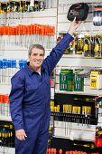 Portrait of confident mature worker reaching for bit case in shop