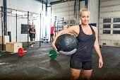 Portrait of confident woman carrying medicine ball in gym