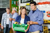 Portrait of happy couple buying tools at hardware store with customers in background