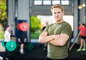 Portrait of confident male athlete standing arms crossed at gym