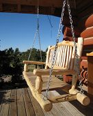 stock photo of log cabin  - Wooden swing on the porch of a log cabin in the country - JPG