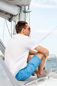 vacation, holidays, travel, sea and people concept - man in sunglasses sitting on yacht deck