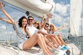 vacation, travel, sea, friendship and people concept - smiling friends sitting on yacht deck and gre