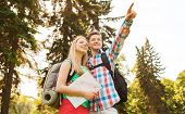 hiking, travel, vacation and friendship concept - smiling couple with map and backpack in nature