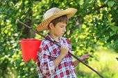 Boy wearing straw hat holding something in arm