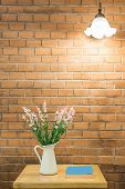 Vase Of Flower And Book On Table With Light Hang On Wall