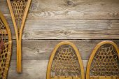 vintage Huron and Bear Paw snowshoes against grained wood planks with a copy space