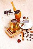 sweet hot drink : black arabic coffee in small white cup with mortar and pestle , bag full beans, co