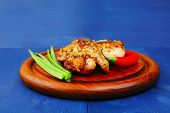 roast meat : chicken legs garnished with green onion pens and peppers on wooden plate over blue wood