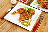 roast chicken : legs garnished with green peas , peppers , and cutlery on white plates over wooden t