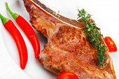 meat food : roast rib on white dish with thyme twig , pepper and tomato isolated over white backgrou