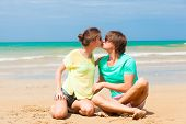 happy young couple kissing at tropical beach