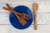 High angle shot of a blue speckled plate with wooden utensils on a rustic farmhouse style kitchen ta