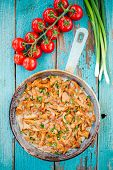 stock photo of chanterelle mushroom  - fried chanterelle mushrooms with green onions in a frying pan on rustic background - JPG