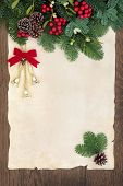 Christmas and winter background border with bells, fir, red berry sprays, mistletoe and pine cones o