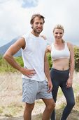 Attractive fit couple standing on mountain trail smiling at camera on a sunny day