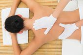 Peaceful brunette enjoying an exfoliating back massage in the health spa