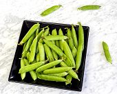 Pods Of Peas On A Black Plate