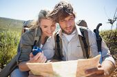 Hiking couple taking a break on mountain terrain using map and compass on a sunny day