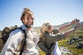 Hiking couple standing on mountain terrain taking a selfie on a sunny day