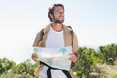 Handsome hiker holding map on mountain trail on a sunny day