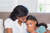 Concerned mother cuddling sick daughter at home in living room