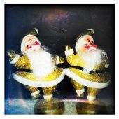 Instagram filtered style image of two glittery gold vintage dancing Santa Claus