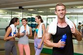 Fit man smiling at camera in busy fitness studio at the gym