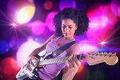 Pretty girl playing guitar against digitally generated cool nightlife design