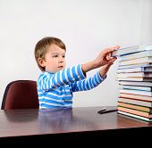 Little Boy Takes A Book From The Stack