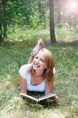 Beautiful Girl Reading Lying On The Grass In The Forest  Whith Lens Flare Effect