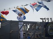 STATEN ISLAND, NY - MAY 25, 2014: A U.S. Navy sailor stops to salute and present his I.D. card on th