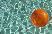 Orange inflatable beach ball floating in pool