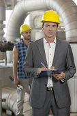 Portrait of young male manager writing on clipboard with manual worker in background at industry