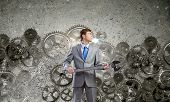 Young determined businessman with wrench in hands and cogwheels at background