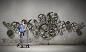 Young businessman with wrench against mechanism background