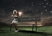 Young woman sitting on bench and playing violin