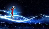 Young woman in red dress against night city background