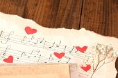 Dried rose flower on music book, close-up, on wooden background