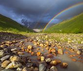 Summer landscape with a rainbow in the mountains above the river. Zemo Svaneti, Georgia