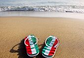 Flip Flops With The Word Italy On Beach Sand - Holidays And Relaxation Concept