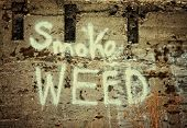 a concrete wall painted with the text smoke weed on it in white spray paint