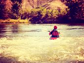 a woman kayaking on a rough river during fall toned with a retro vintage instagram filter