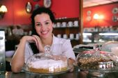 Owner Of A coffee shop Showing Her Tasty Cakes
