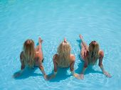 Three young attractive women relaxing at the swimming pool in the summertime