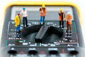 stock photo of ohm  - Team of miniature workers on top of multimeter - JPG