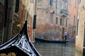 Gondola Sailing Through A Small Canal In Venice.