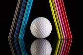 Twelve Different Colors Diaries And Golf Ball On A Glass Desk