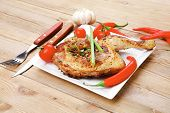 meat food : chicken legs garnished with hot chili peppers on white plates over wooden table