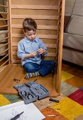 Kid with tools assembling a new furniture